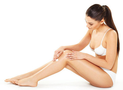 Young woman applying body cream on legs